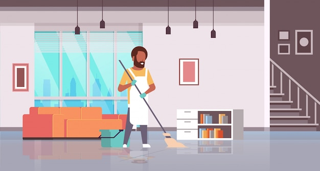 Man in gloves and apron washing floor   guy using mop doing housework cleaning concept modern house living room interior  horizontal full length
