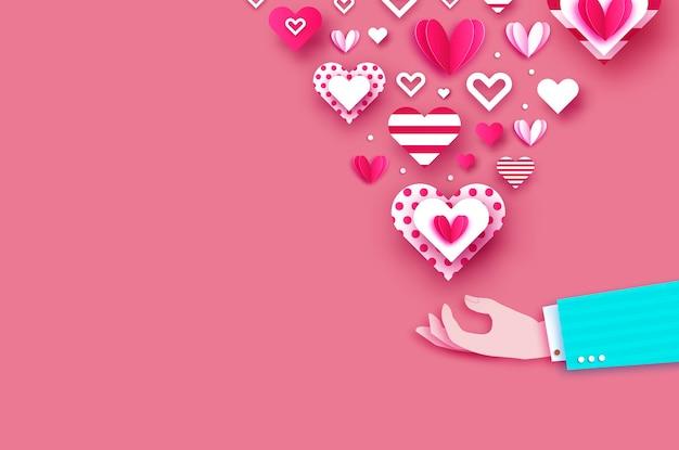 愛のマッサージとして愛の心を持つ男の手。あなたの愛を分かち合いましょう。ペーパーカットスタイル。バレンタイン・デー。 2月14日。