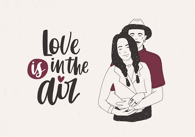 Man in hat standing behind woman with braids and embracing her and love is in the air lettering on white