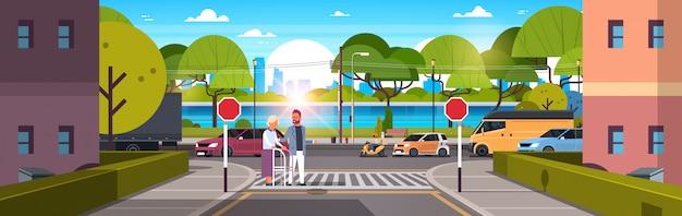 Man help senior woman with walking stick crossing street