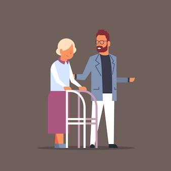 Man helping senior woman with walking frame