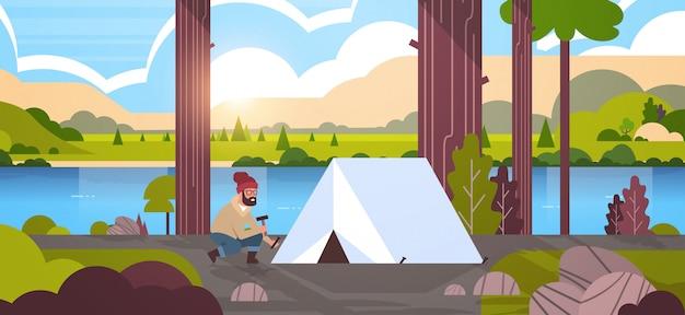 男ハイカーキャンピングカーキャンプハイキングコンセプトの日の出風景自然川山のキャンプの準備テントをインストールします。