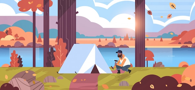 Man hiker camper installing tent preparing for camping hiking concept sunrise autumn landscape nature river mountains background  horizontal full length