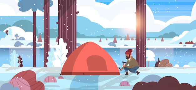 Man hiker camper installing tent preparing for camping hiking concept sunrise winter snowfall landscape nature river mountains