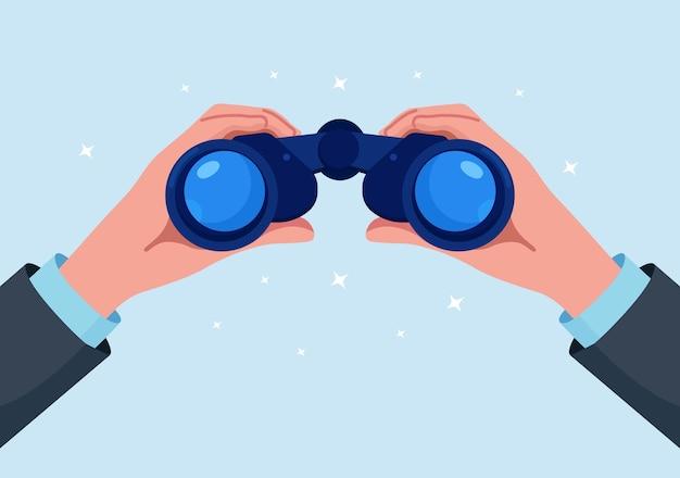 Мужчина держит в руке бинокль и смотрит далеко вперед. человек внимательно за кем-то наблюдает. наблюдение, открытие, концепция будущего. поисковая система или исследование, веб-серфинг