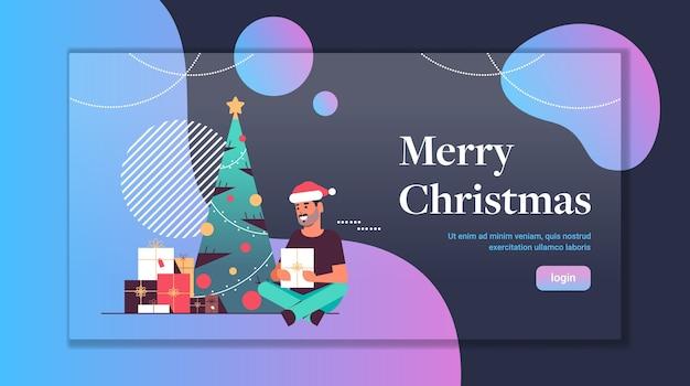 Man holding gift present box merry christmas happy new year holiday celebration concept guy wearing santa hat sitting near fir tree flat