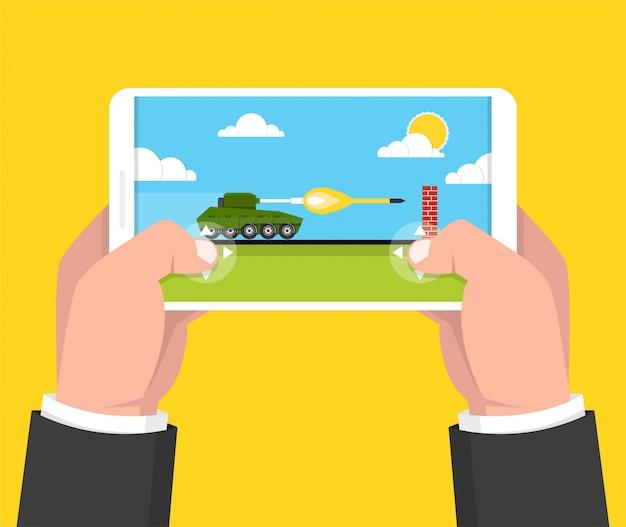 スマートフォンを押しながらタンクゲームで遊ぶ男