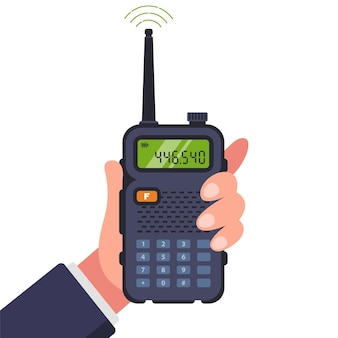 Man holds a walkie-talkie in his hand for communication.
