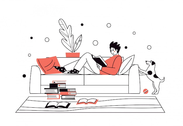 Man at home, lying on the sofa, reading books. home library. the concept of reading paper literature. young adult man having a rest with good book. boy enjoying himself at home.