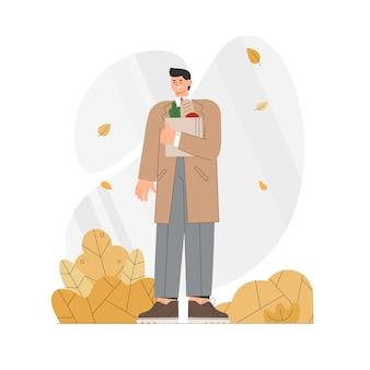 コートを着た男は、秋に食物と一緒に紙袋を保持しています。