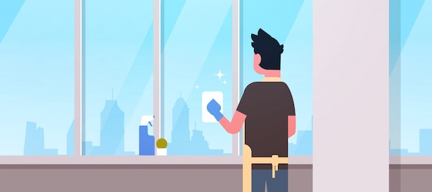 手袋とエプロンの窓拭きと布クリーナースプレーリアビュー男家事コンセプトモダンなアパートメントのリビングルームのインテリアをやっている男