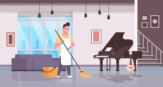 手袋とエプロン洗浄床男モップを使用して家事掃除のコンセプトモダンな家のリビングルームのインテリアのクリーニングを使用している人