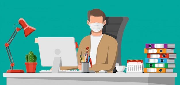 彼のコンピューターに取り組んでいる医療マスクの男