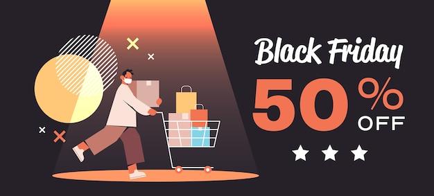 ショッピングバッグとトロリーカートを押す保護マスクの男ブラックフライデー大セールプロモーション割引コロナウイルス検疫コンセプト