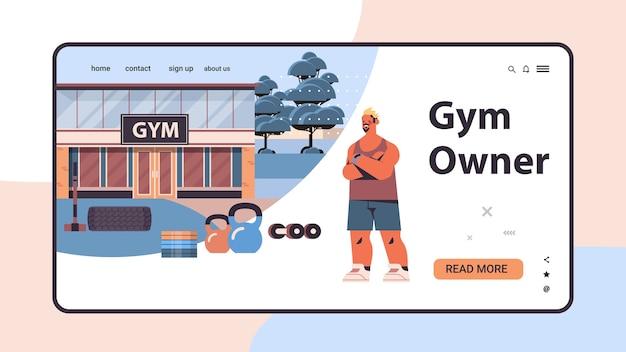 Человек в спортивной одежде с различными инструментами, стоящий возле здания тренажерного зала, фитнес-тренинг, концепция здорового образа жизни, копирование пространства