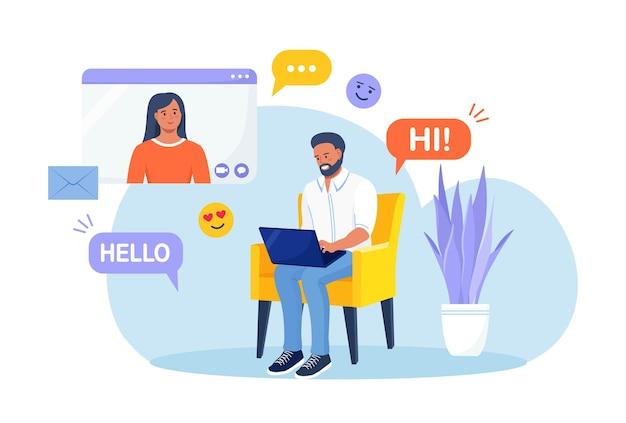 Мужчина сидит в кресле и использует ноутбук для видеозвонка с подругой или коллегой. друзья разговаривают в сети. онлайн-образование и электронное обучение. социальные сети или приложение для знакомств и виртуальные отношения