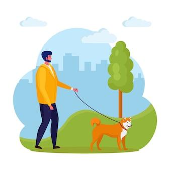 男は犬を連れて歩いています。幸せな少年はペットと遊ぶ。背景に鎖の子犬。