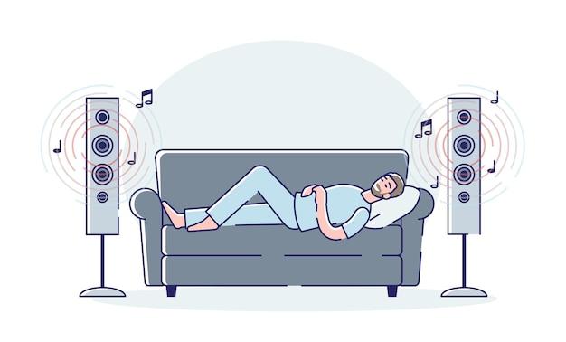 Человек громко слушает музыку из современных звуковых колонок, лежа на тренере дома