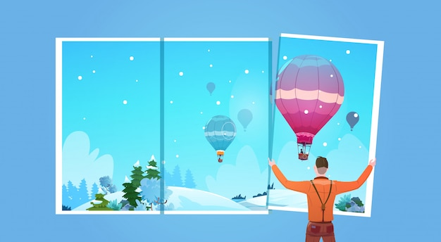 Man looking in window at colorful air balloons flying in winter sky