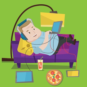 Man lying on sofa with many gadgets.