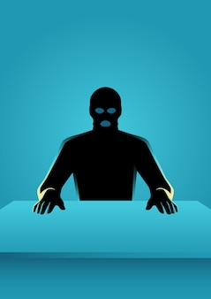 Man in mask sitting in front of a table