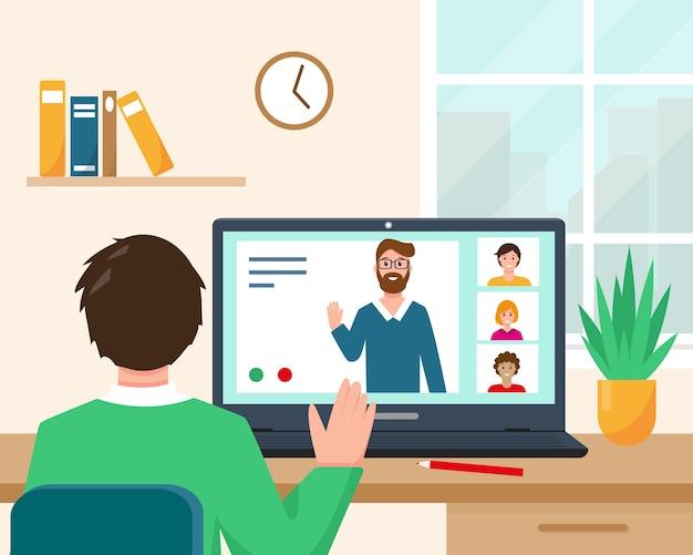 Человек возле стола и ноутбука с людьми на экране