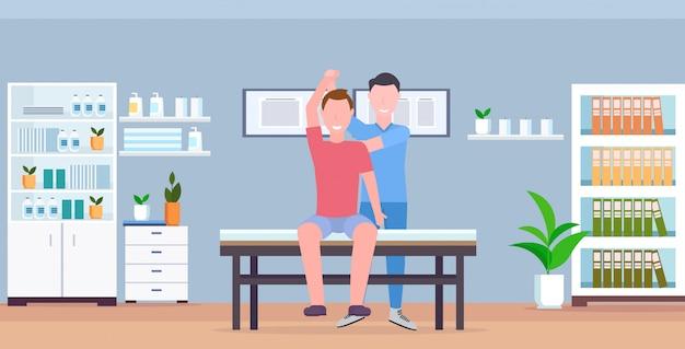 남자 환자 치료 치료 마사지 환자의 몸 수동 스포츠 물리 치료 개념 현대 클리닉 병실 내부 수평을하고 테이블 안마사 치료사에 앉아