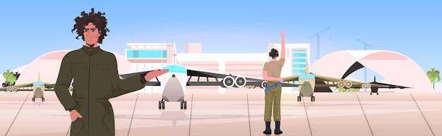 Пилот человек в униформе указывая на самолет аэровокзальный терминал концепция авиации портрет горизонтальный