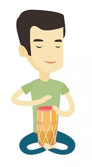 Человек играет этнический барабан.