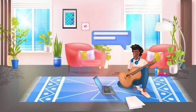 기타를 연주하고 노트북 소셜 미디어 네트워크 채팅 거품 커뮤니케이션 개념을 사용하는 남자