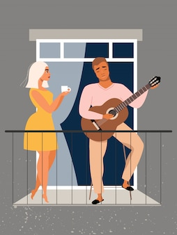 Man plays guitar at the balcony. love couple. quarantine and self-isolation concept. family staying at home during the pandemic. beautiful couple in the window. man and woman standing at the balcony.