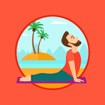 Man practicing yoga upward dog pose on the beach.