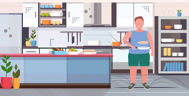 Man preparing fresh pancakes in frying pan unhealthy nutrition obesity concept overweight guy standing pose modern kitchen interior  full length horizontal