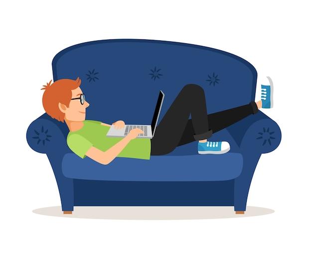 Человек расслабляющий на диване и с помощью ноутбука