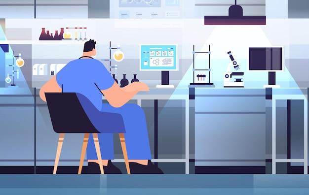 실험실에서 화학 실험을 만드는 실험실 연구원의 테스트 튜브로 작업하는 남자 연구 과학자