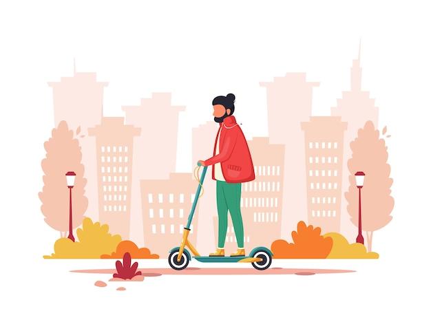 秋に電動キックスクーターに乗る男。エコ輸送のコンセプト。