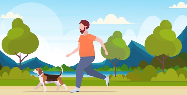 Man running with dog guy training workout weight loss concept summer park landscape background  full length horizontal