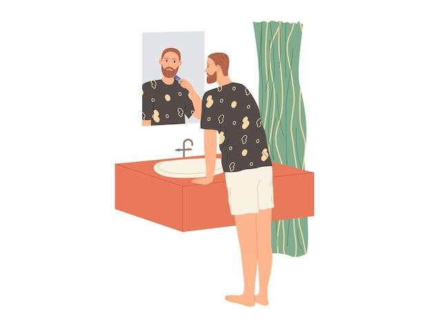 남자는 거울 옆 욕조에 서서 전기 면도기로 수염을 면도합니다.