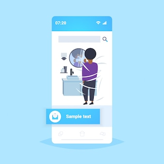 Man shaving his face african american guy looking at mirror modern home bathroom interior smartphone screen mobile app  full length rear view