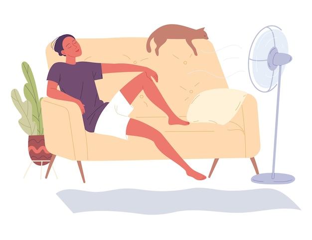 男は家でファンのそばのソファに座り、暑い日の新鮮さを楽しんでいます。