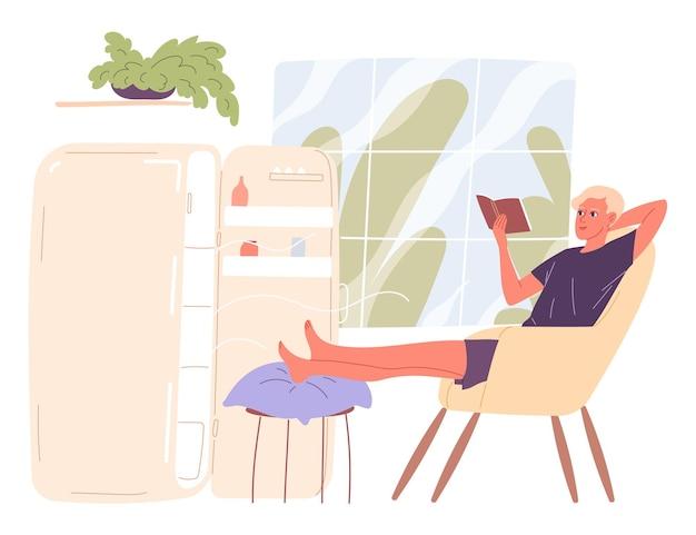남자는 열린 냉장고 옆에 앉아서 더위를 식힙니다.