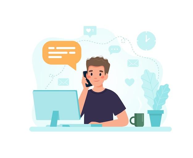 Человек сидит за столом с компьютером, отвечая на звонок.