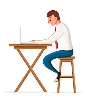 机に座ってラップトップで作業している男