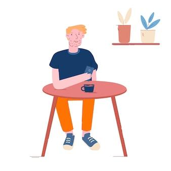 コーヒーを飲みながらテーブルに座っている男