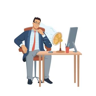 コンピューターと文房具のファンが眼鏡をかけて彼のビジネスマンを吹いてテーブルに座っている男
