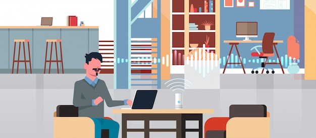 Человек сидя на рабочем месте с ноутбуком, используя интеллектуальный умный динамик с распознаванием голоса концепция искусственного интеллекта помощь современное рабочее пространство квартира горизонтальный портрет