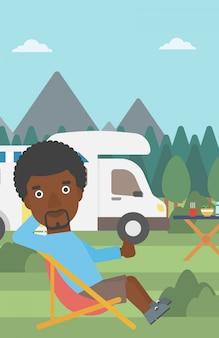 Man sitting in chair in front of camper van.