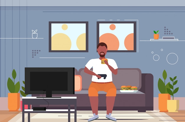 Man sitting on couch eating hamburger using joystick game pad overweight guy plying video games on tv unhealthy lifestyle concept living room interior  horizontal full length