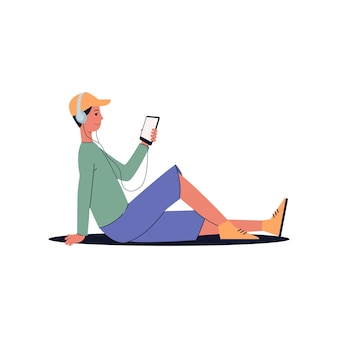 Man sitting on the floor with headphones listening to music and looking at his phone screen while smiling - audio listener with smartphone,
