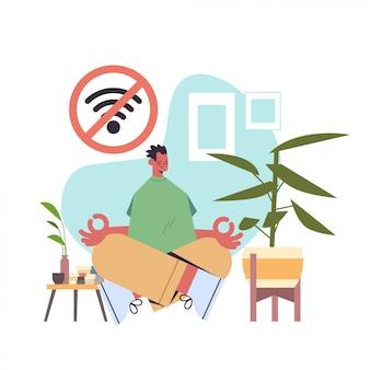 남자 앉아 로터스 포즈 디지털 해독 오프라인 활동 개념 가제트없이 시간을 보내는 사람